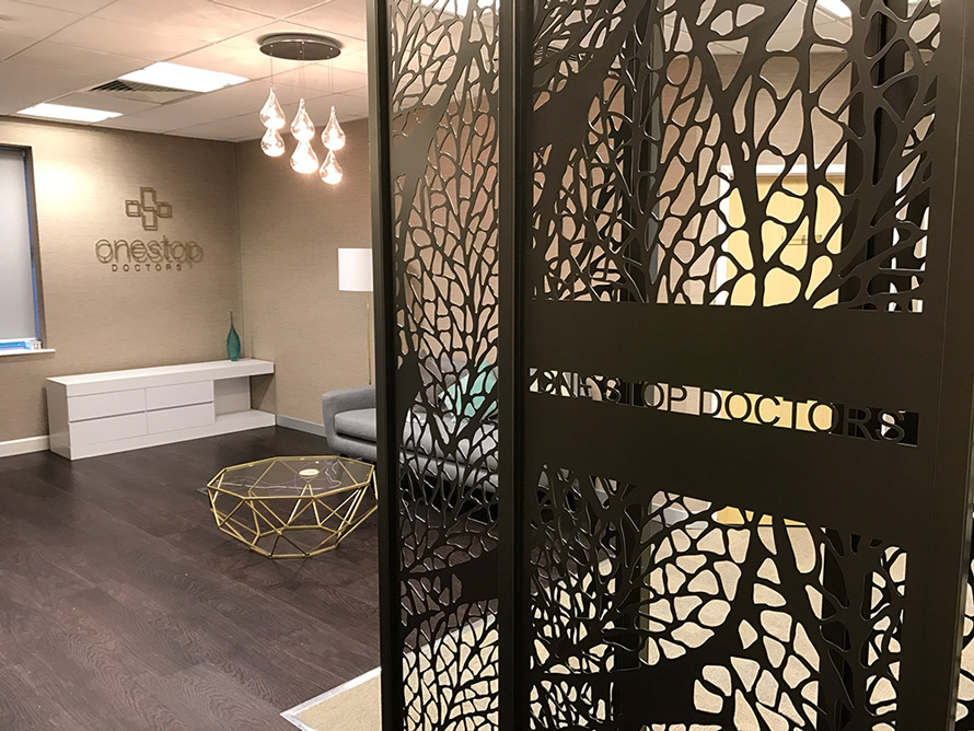 Decorative reception screens in doctors entrance hall with company logo in laser cut metal. Modern room dividers in one stop doctors logo on wall in head offiice