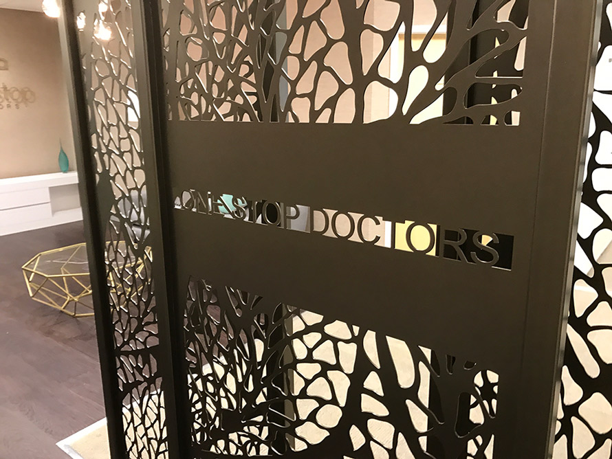 Decorative reception screens in doctors entrance hall with company logo in laser cut metal