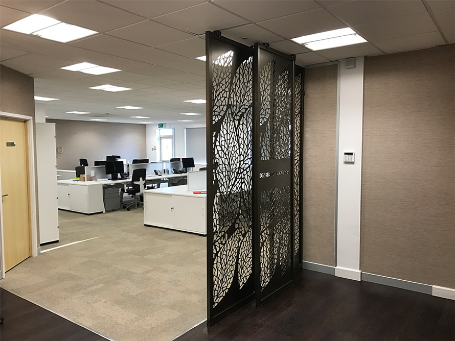 Decorative reception screens in doctors entrance hall with company logo in laser cut metal. Modern room dividers in one stop doctors head office